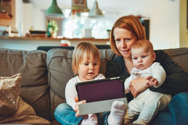 moeder met 2 baby's op de bank met een tablet